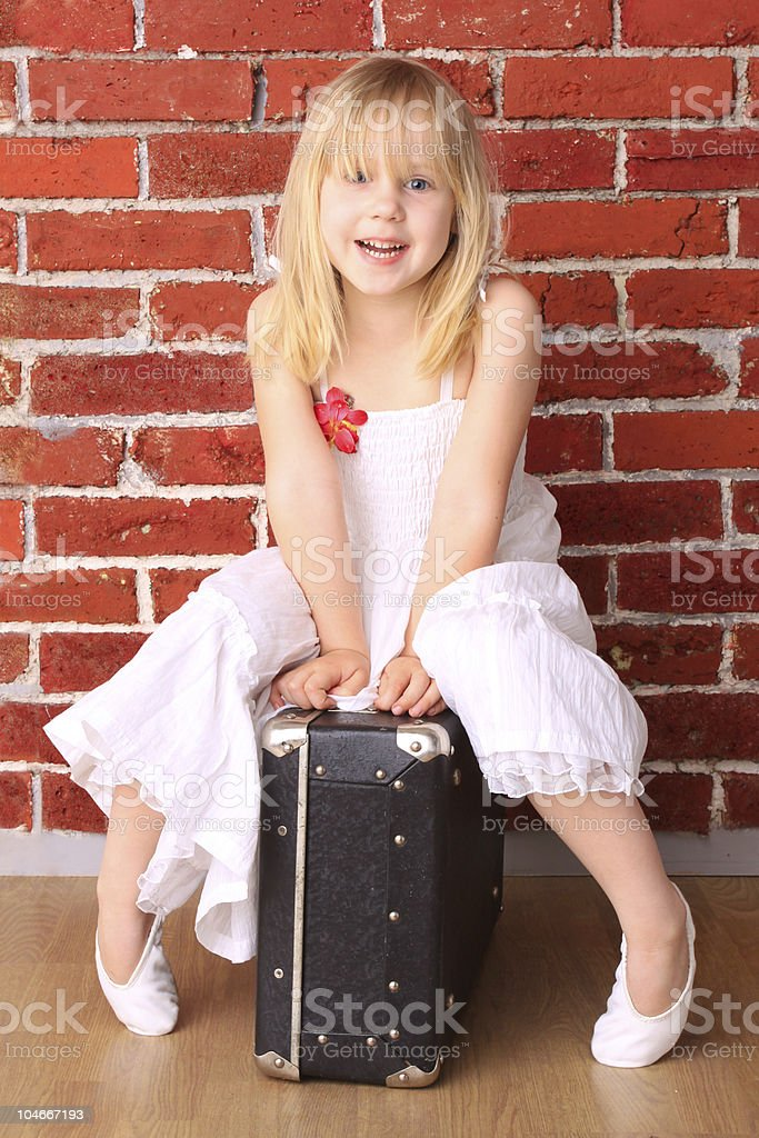 beautiful little girl sitting on a suitcase and laughs royalty-free stock photo