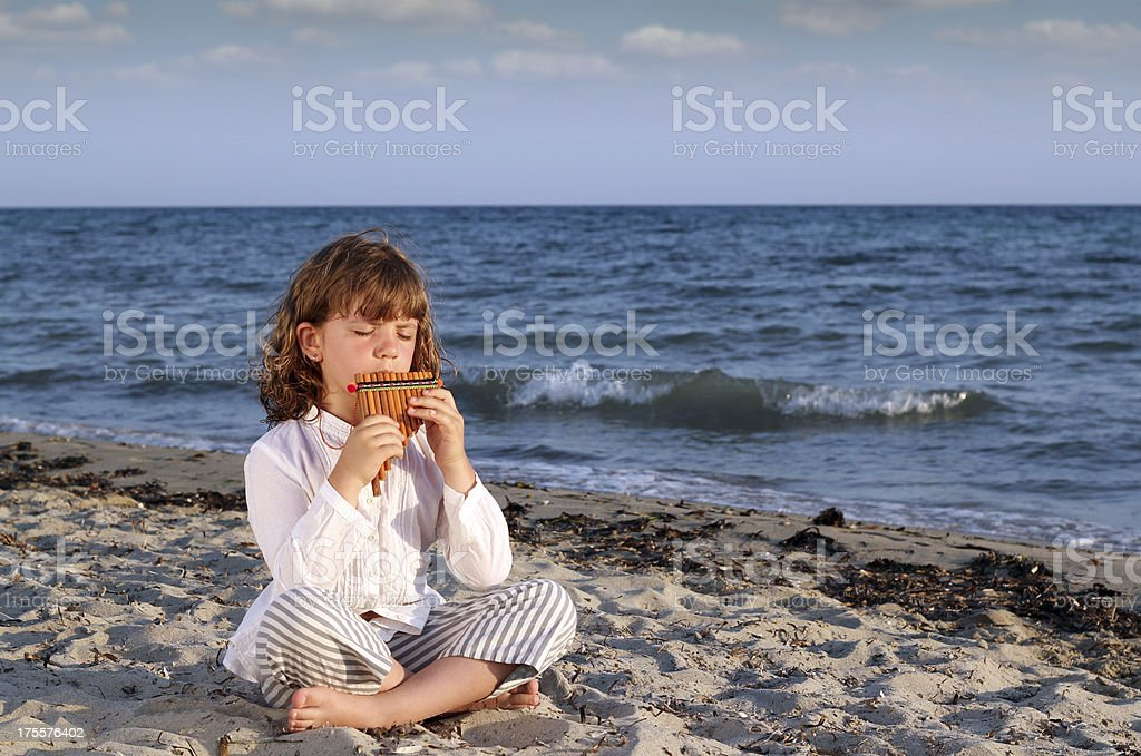 beautiful little girl sitting on beach and play pan pipe stock photo