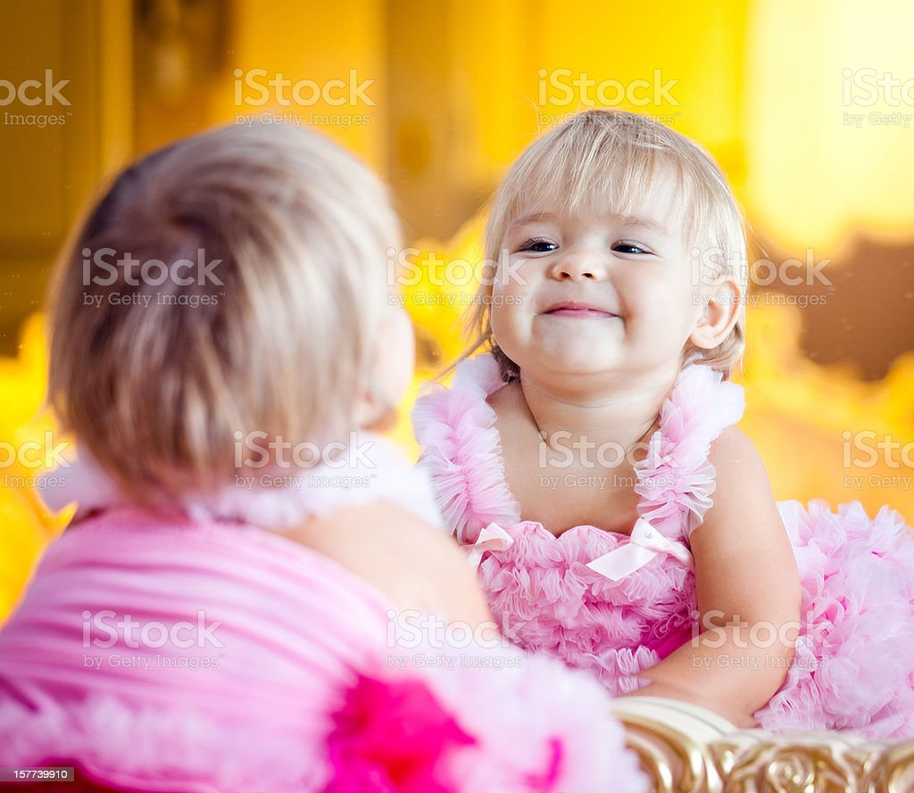 Beautiful little girl smiling at herself in a mirror royalty-free stock photo