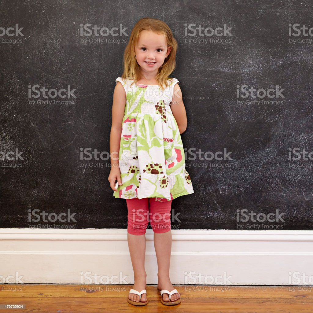 Beautiful little girl standing against blackboard at home stock photo