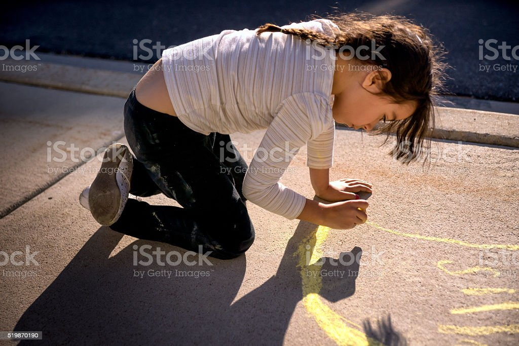 Beautiful Little Girl Using Sidewalk Chalk stock photo
