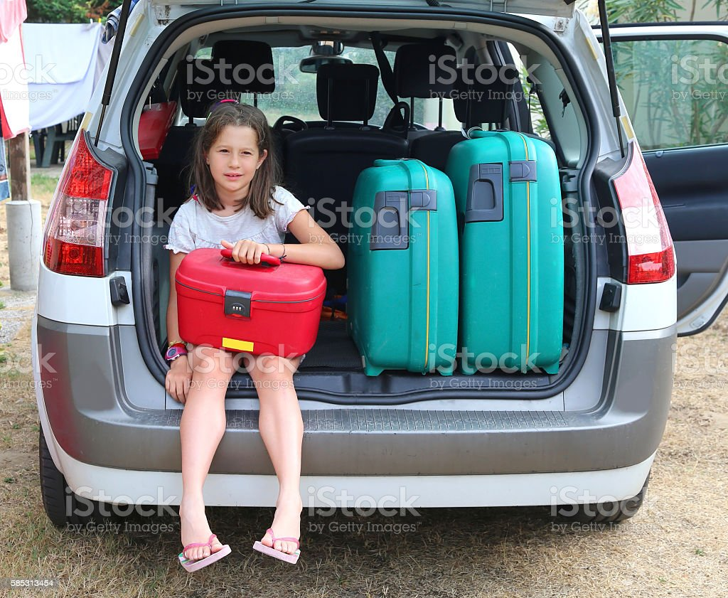 beautiful little girl with brown hair loads the red suitcase stock photo