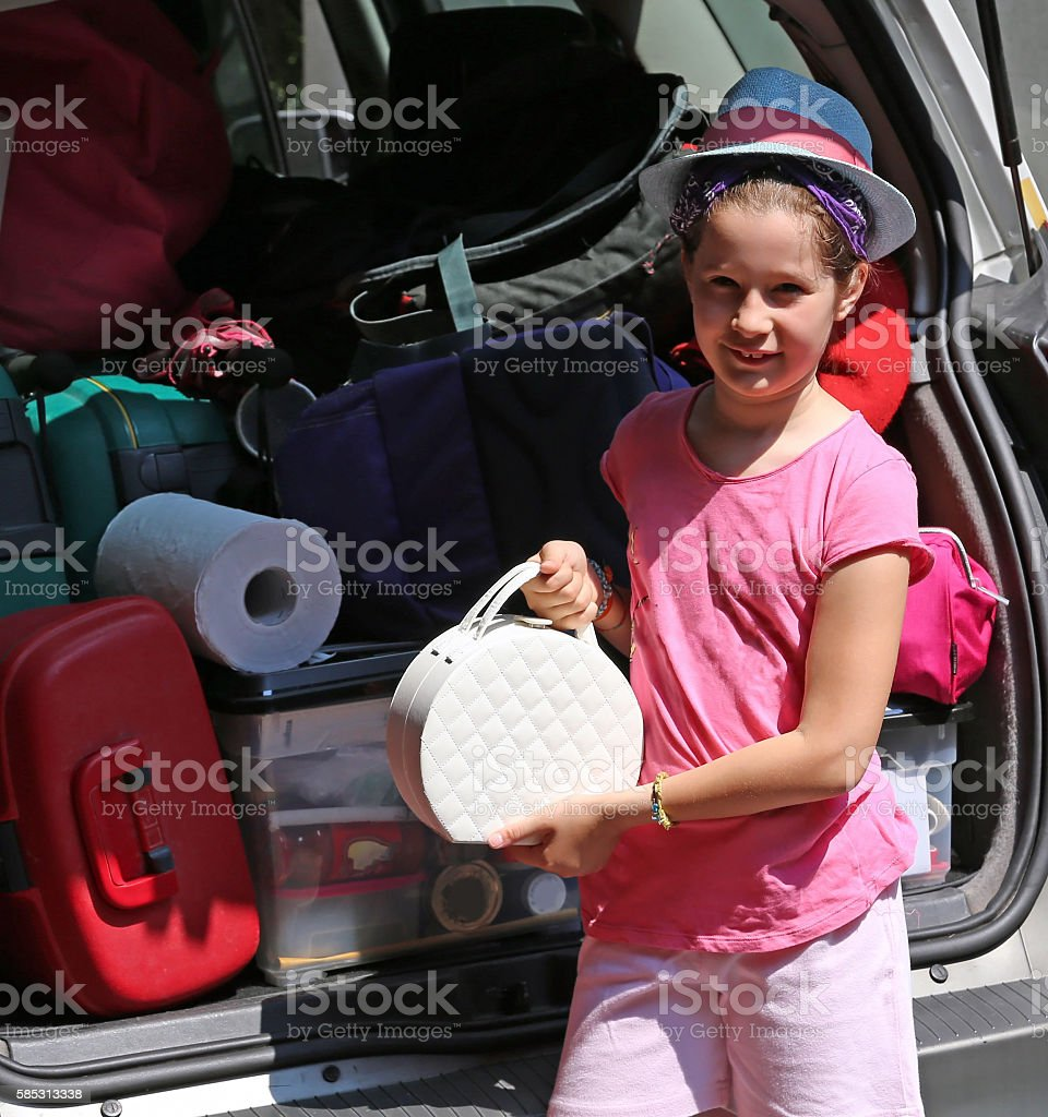 beautiful little girl with Hat loads the trunk stock photo