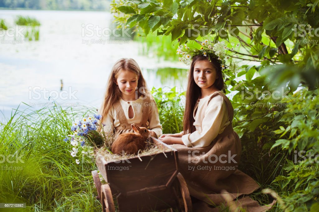 Beautiful little girls in a white dress posing in the grass. Sunset light. stock photo