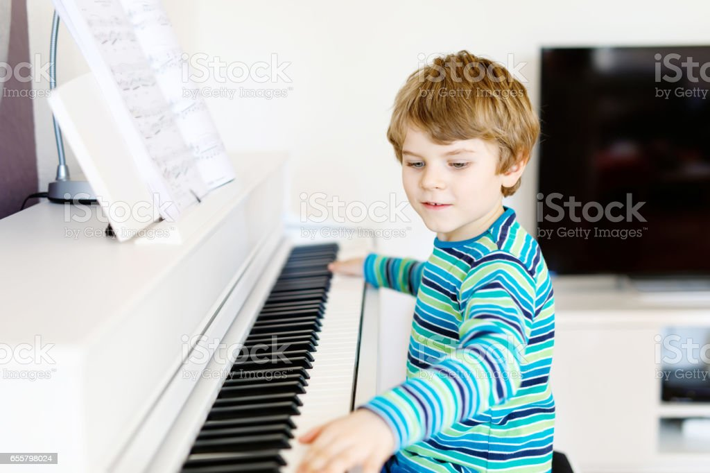 Beautiful little kid boy playing piano in living room or music school stock photo