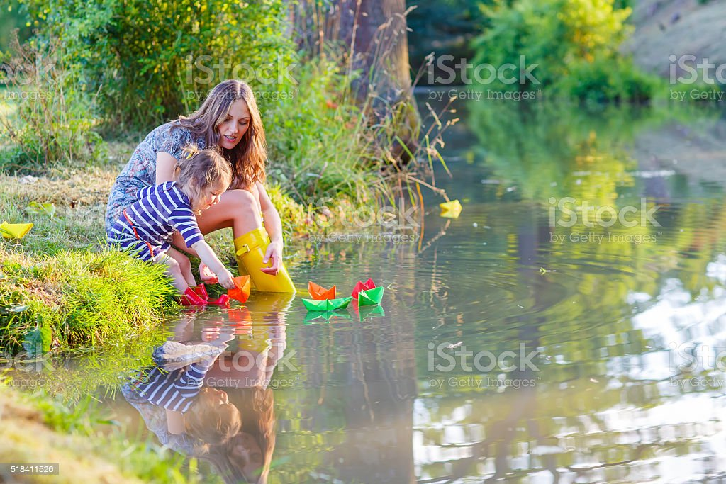Beautiful little kid girl and mother playing with paper boats stock photo