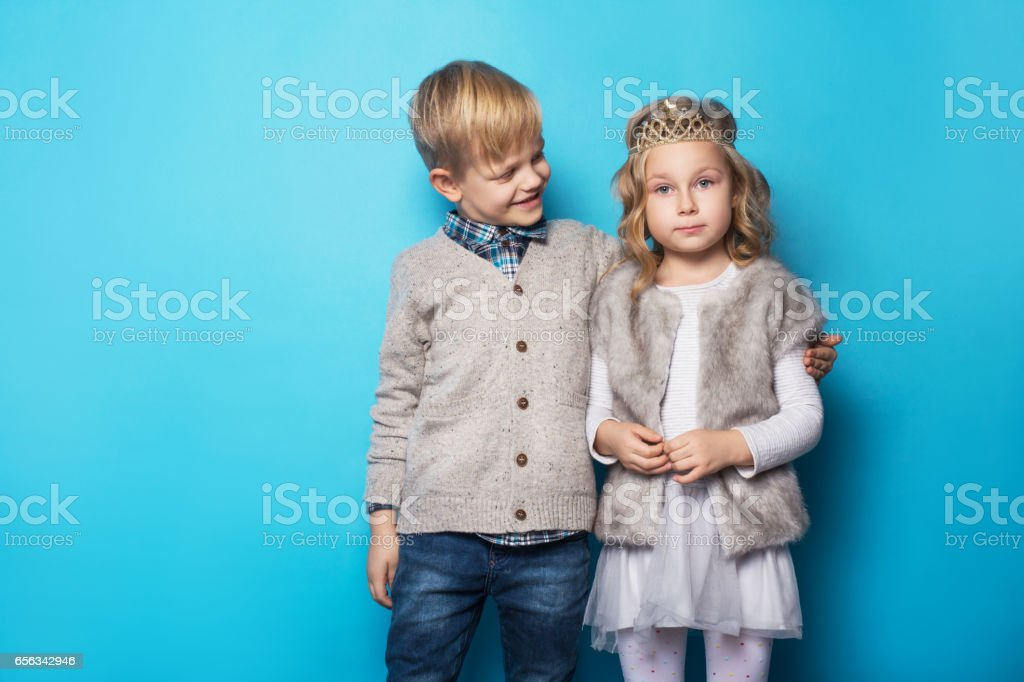 Beautiful little princess and handsome boy. Friendship. Love. Valentine. Studio portrait over blue background stock photo