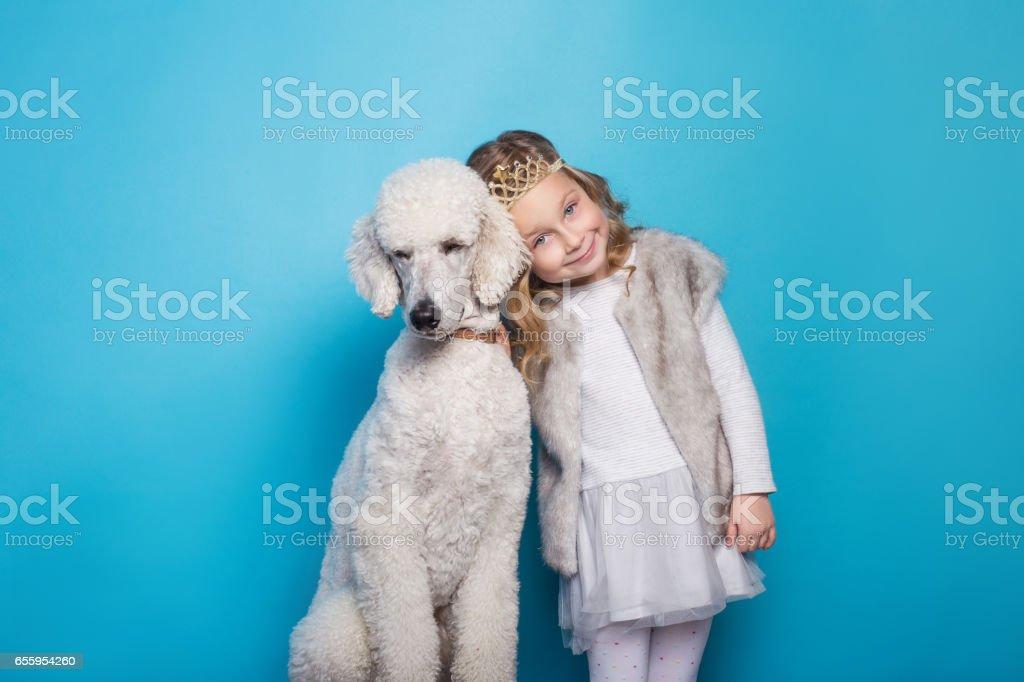 Beautiful little princess with dog. Friendship. Pets. Studio portrait over blue background stock photo