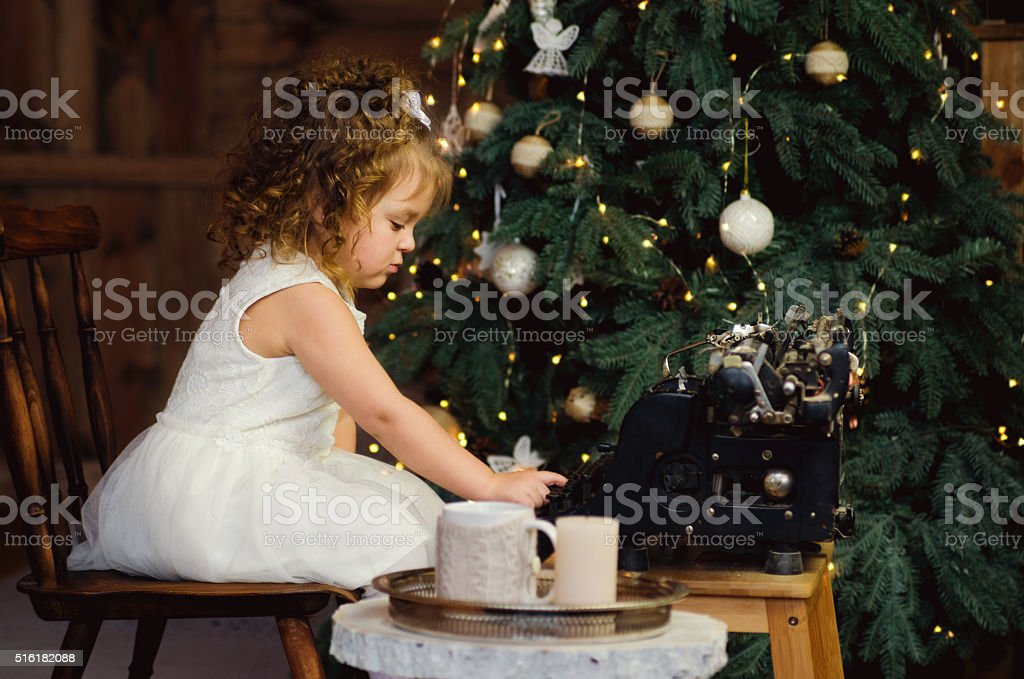 Beautiful little writer in a white dress stock photo