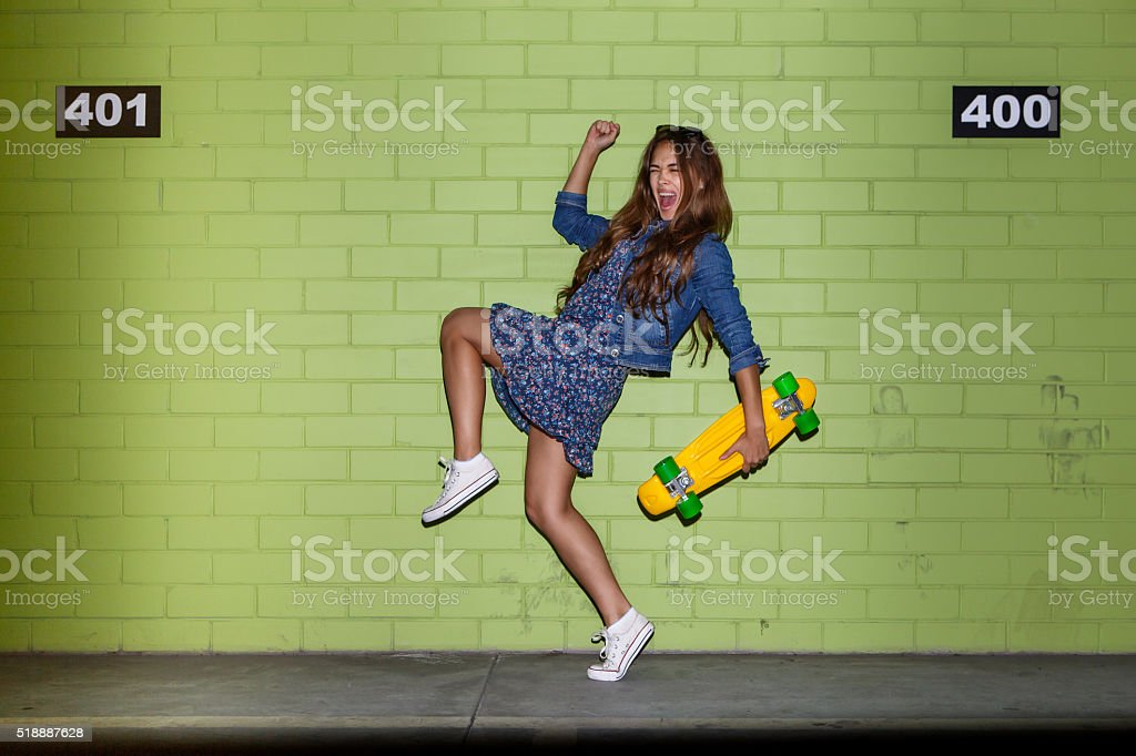 beautiful long-haired girl with penny-board near a green brick wall stock photo