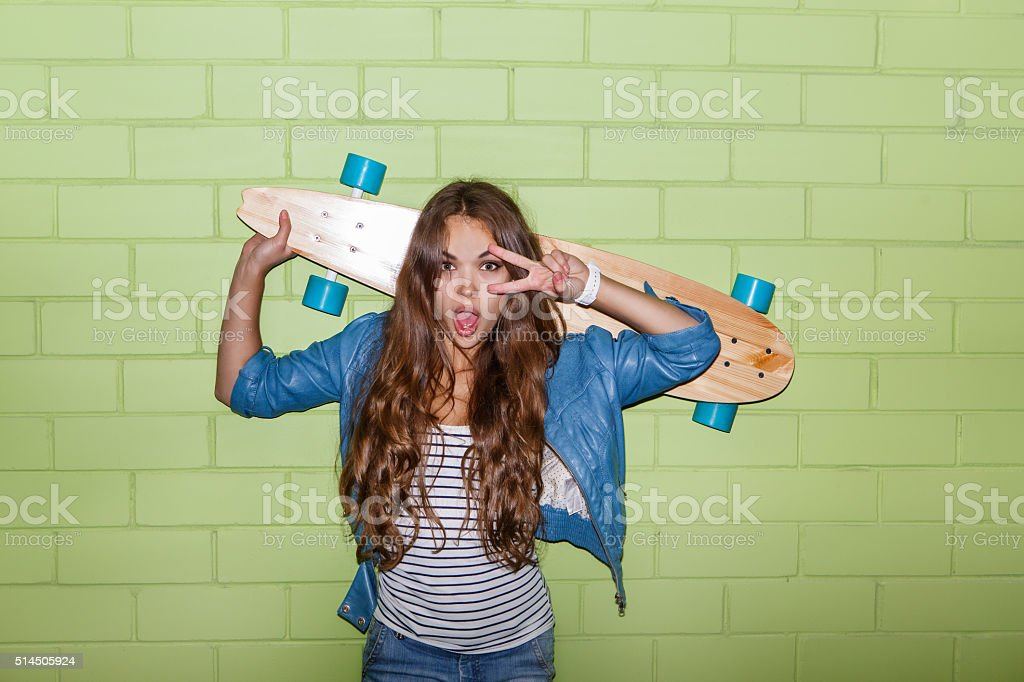 beautiful long-haired lady with wooden longboard near a green wall stock photo