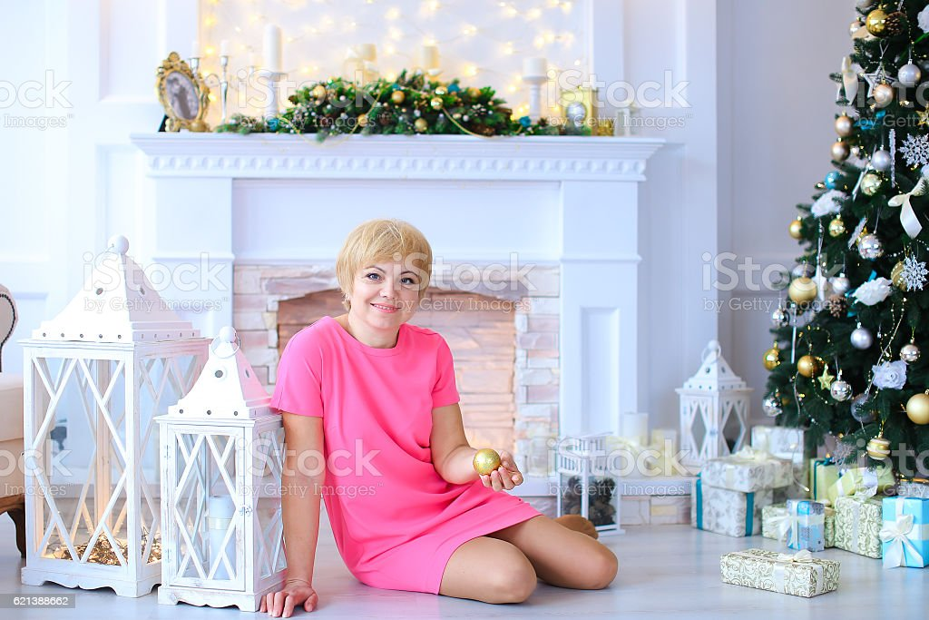 Beautiful lovely woman sitting on floor near lanterns and holds stock photo