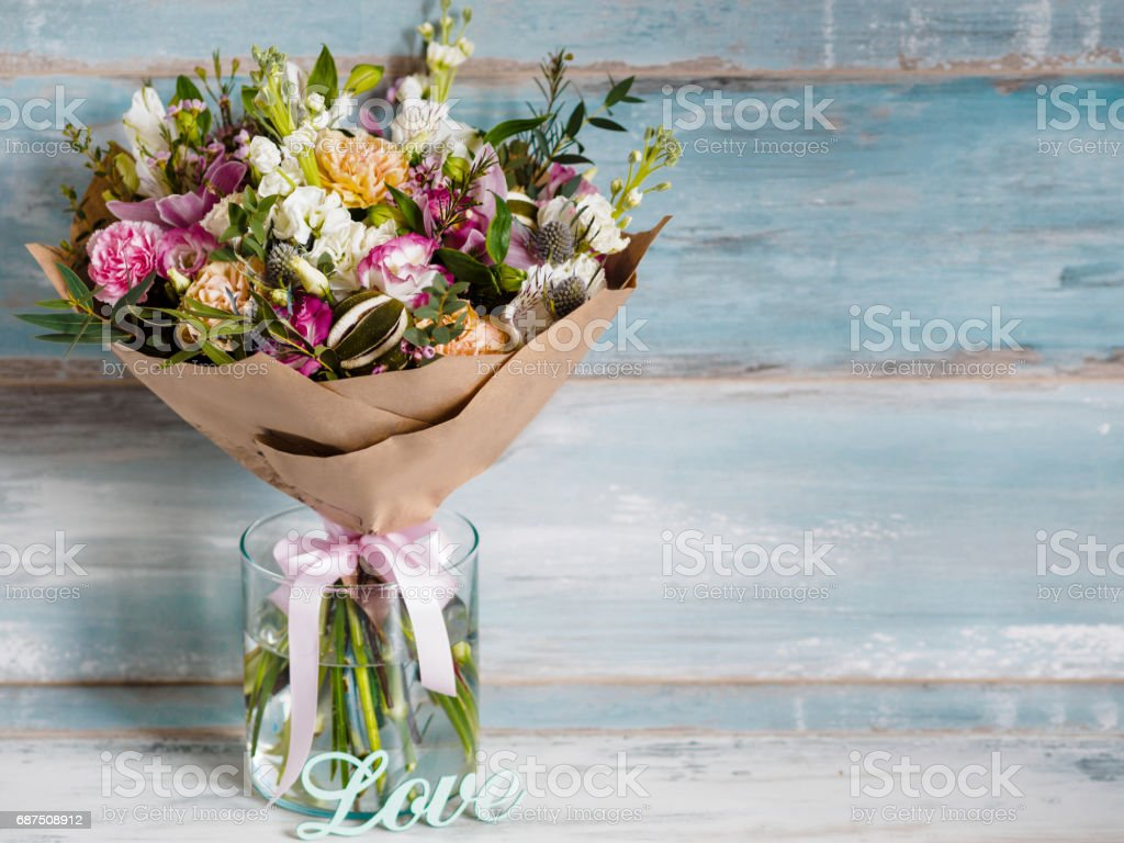 beautiful lush bouquet with different spring flowers, turquoise background, gift stock photo
