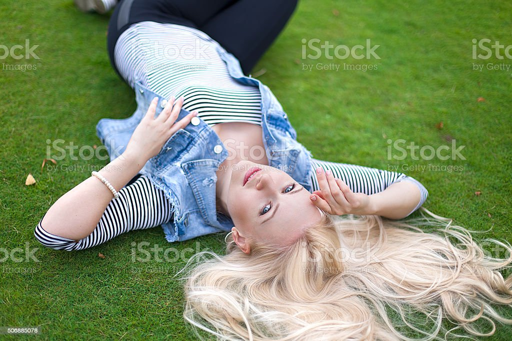 Beautiful lying on the green grass with untressed hair stock photo