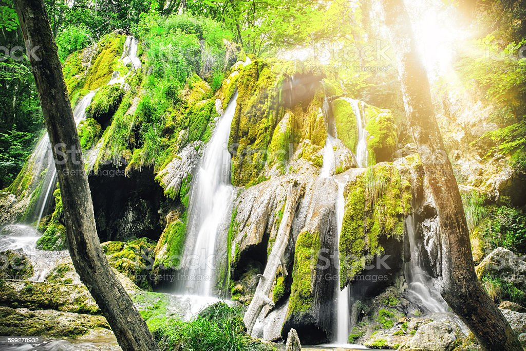 Beautiful majestic fresh waterfall in sunny forest in France stock photo