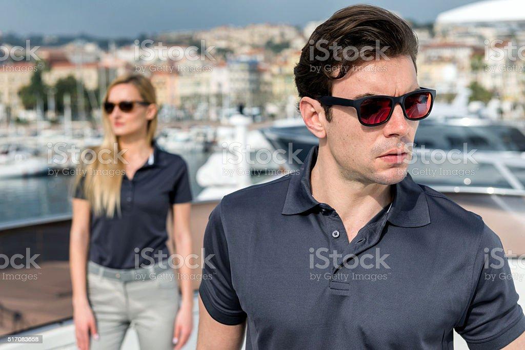 Beautiful man and woman posing on yacht stock photo