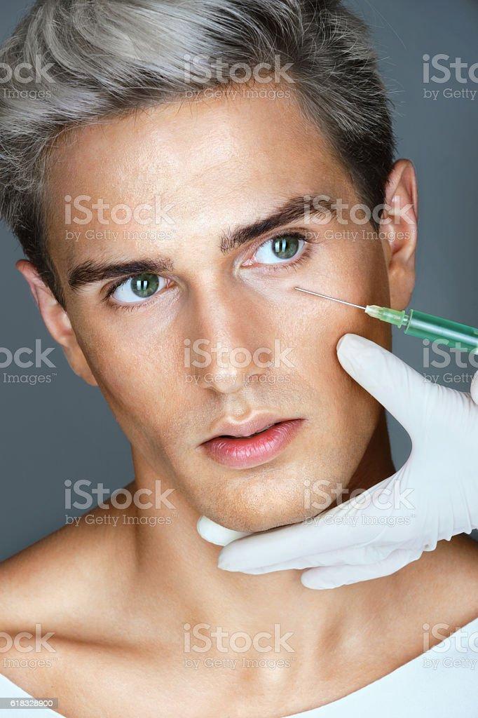 Beautiful man gets beauty facial injections. stock photo