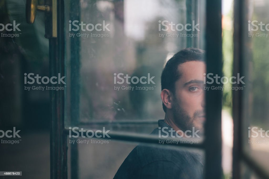 Beautiful Man Watching Through Dirty Window stock photo