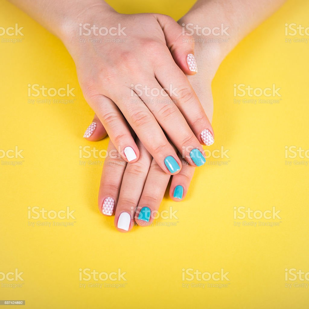 beautiful manicure. gel polish coating in white and turquoise, stamping. stock photo