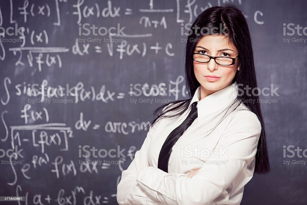 Beautiful math teacher posing in front of a blackboard royalty-free stock photo
