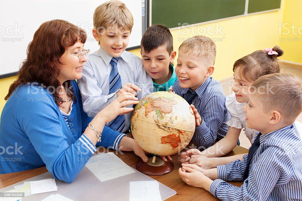 beautiful, mature caucasian teacher in classroom geography in elementary school stock photo