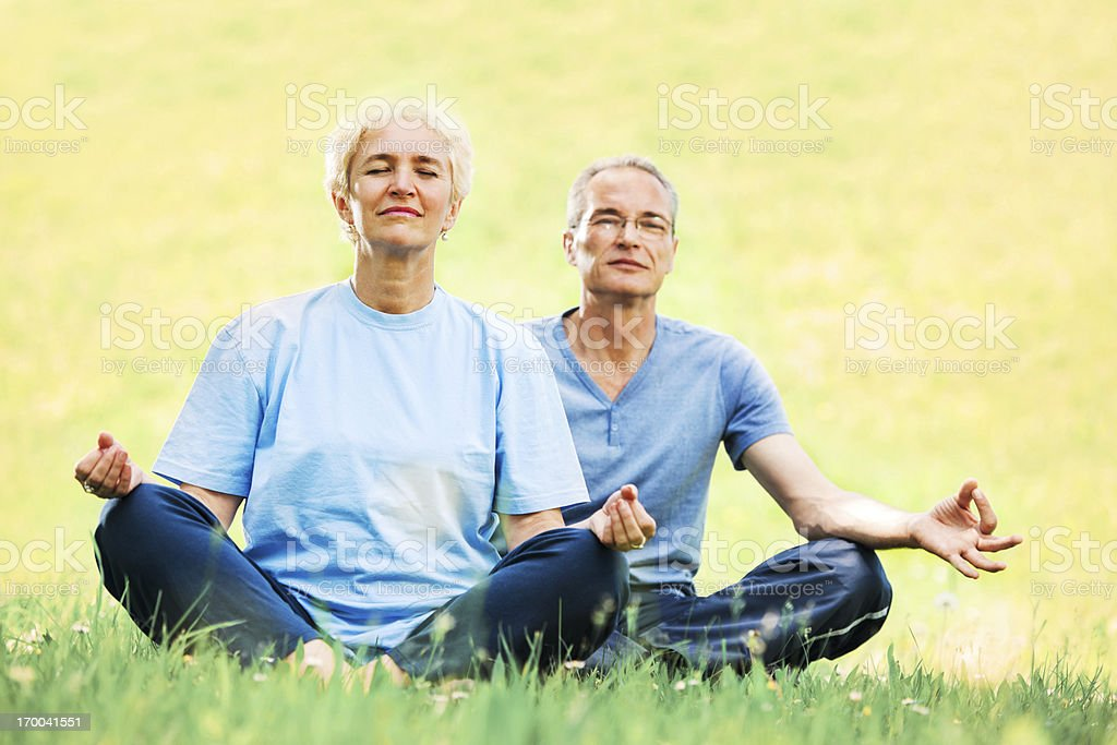 Beautiful mature couple doing yoga outdoors royalty-free stock photo