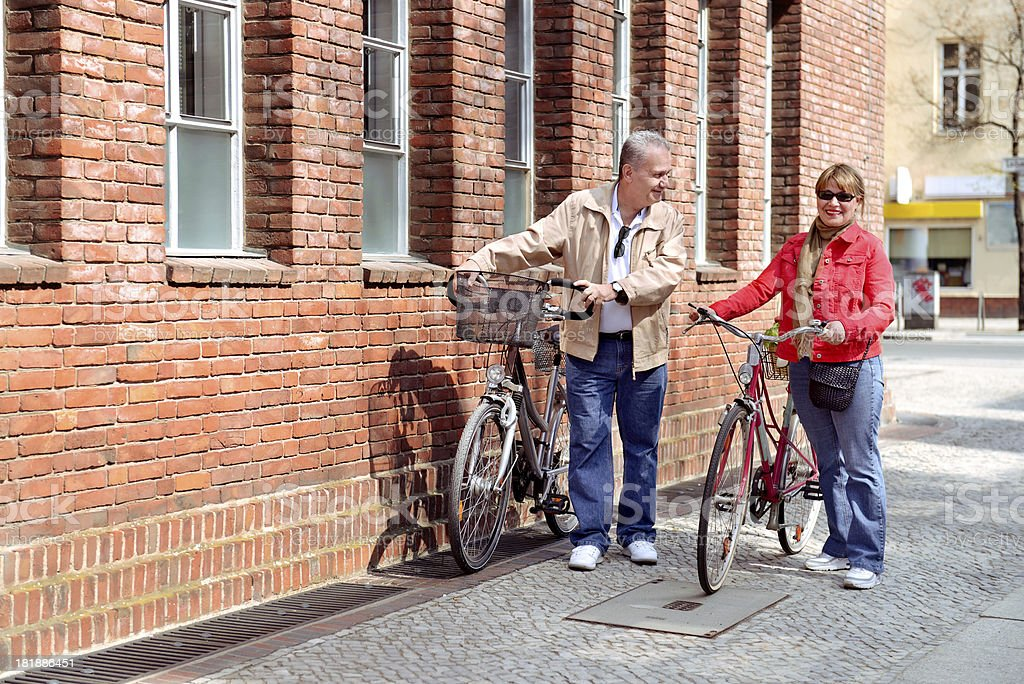 Beautiful mature couple with cycles in the city royalty-free stock photo