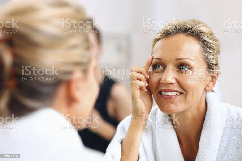 Beautiful mature woman admiring herself in the mirror royalty-free stock photo