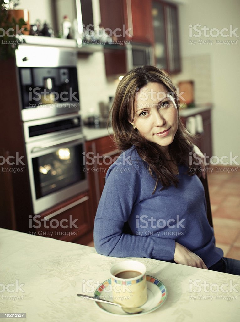 Beautiful Mature Woman drinking coffee in her kitchen stock photo