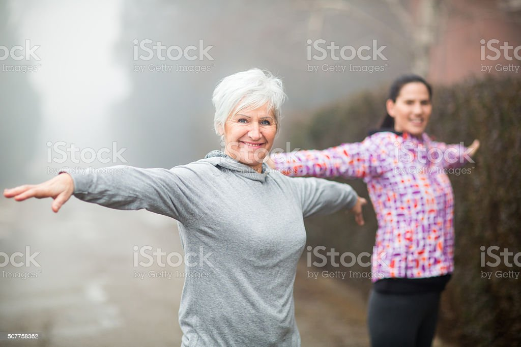 Beautiful Mature Woman Exercising with friend stock photo