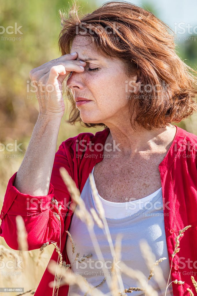 beautiful mature woman having headache for rhinitis outdoors or allergies stock photo