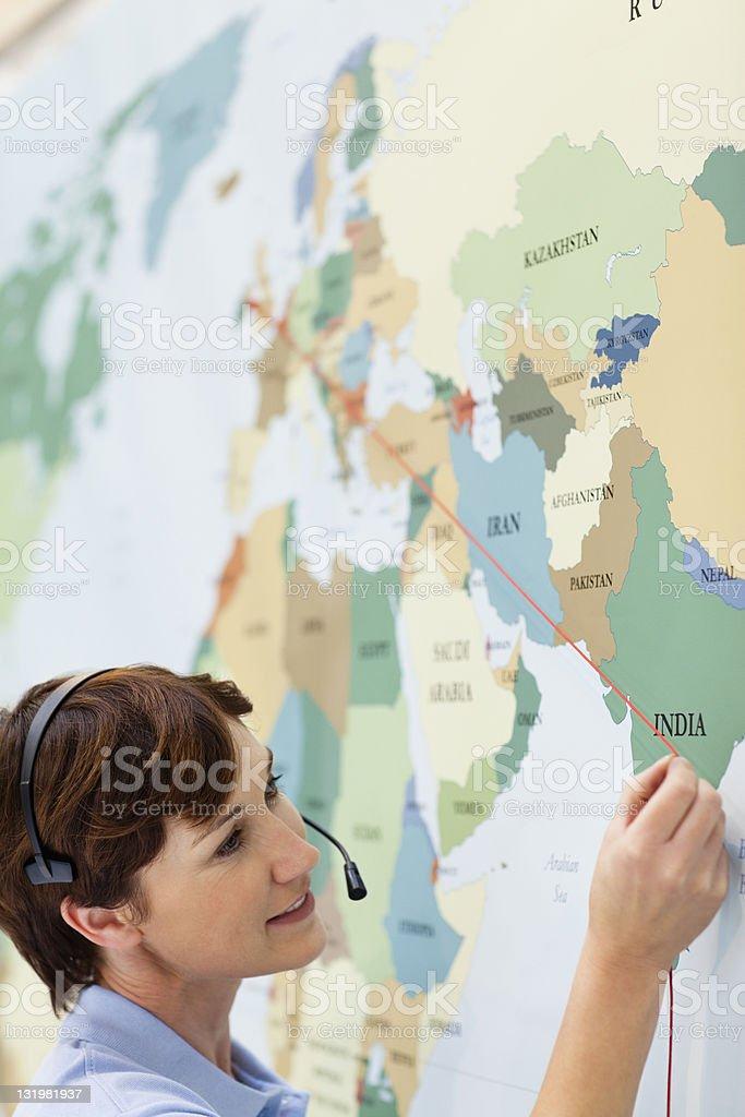 Beautiful mature woman marking a line on world map stock photo