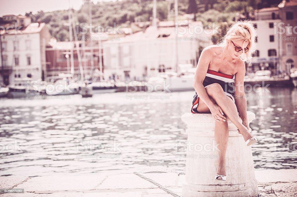 Beautiful mature woman sitting at the sea stock photo