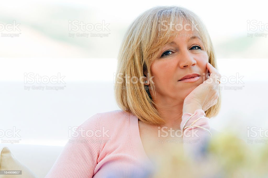 Beautiful mature woman sitting on couch royalty-free stock photo