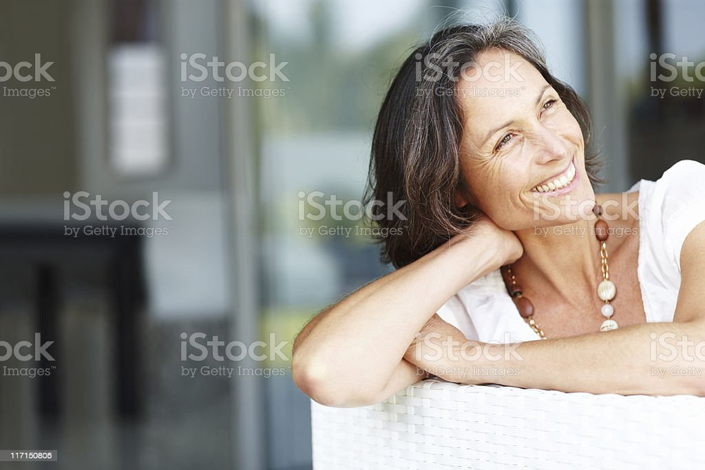 Beautiful mature woman sitting on couch smiling and looking away stock photo