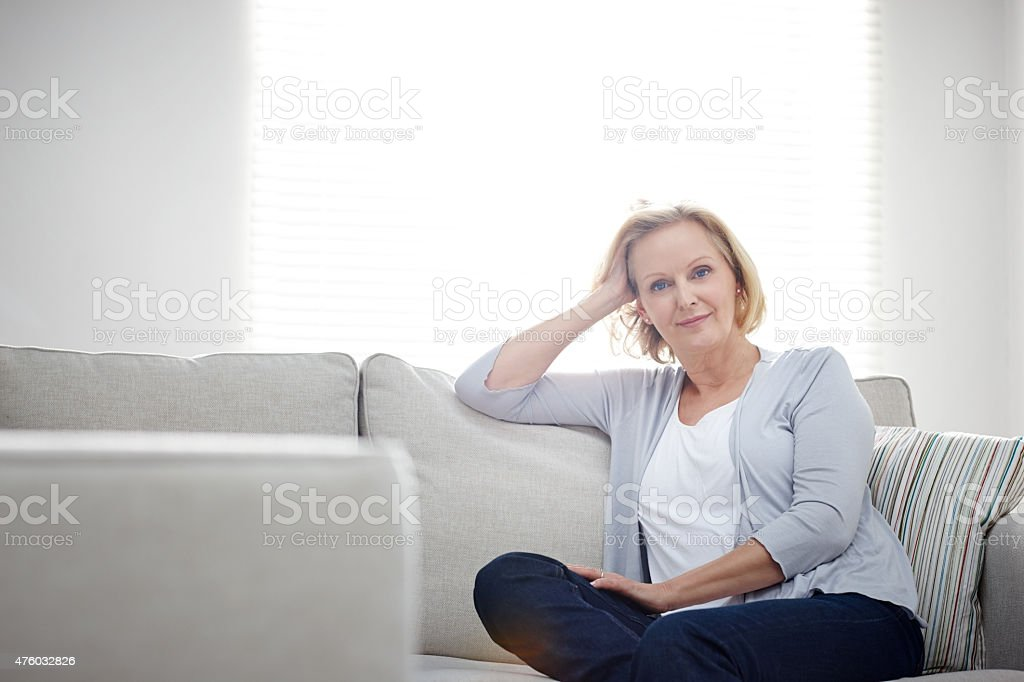 Beautiful mature woman sitting relaxed on a couch stock photo