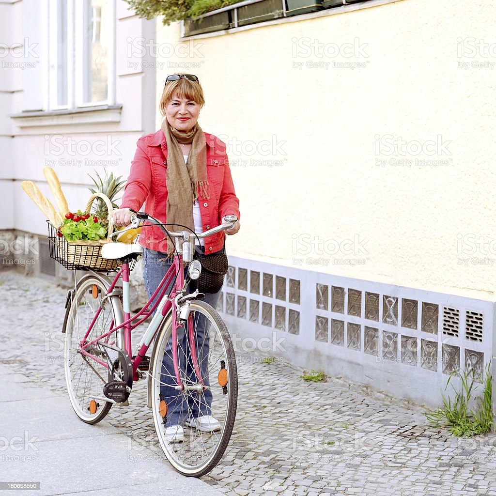 Beautiful mature woman transporting her grocery shopping with cycle royalty-free stock photo