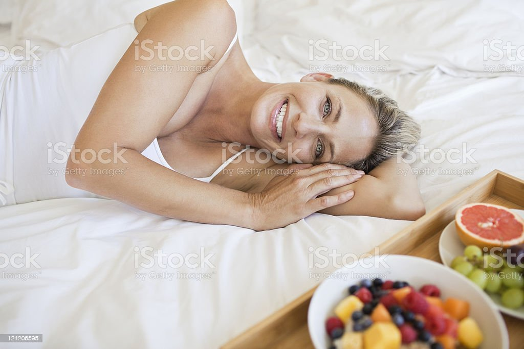 Beautiful mature woman with breakfast on bed royalty-free stock photo