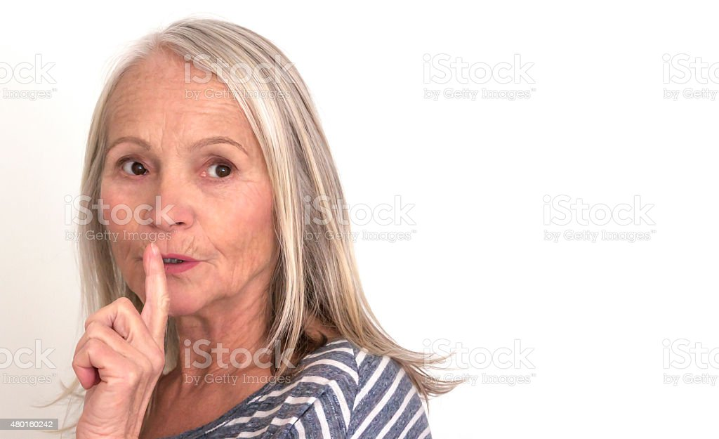 Beautiful mature woman with finger on her mouth, copy space stock photo