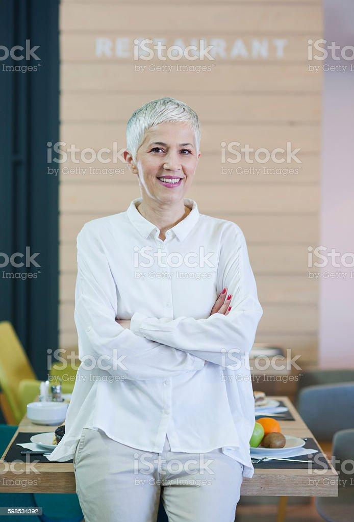 Beautiful mature woman working at restaurant stock photo