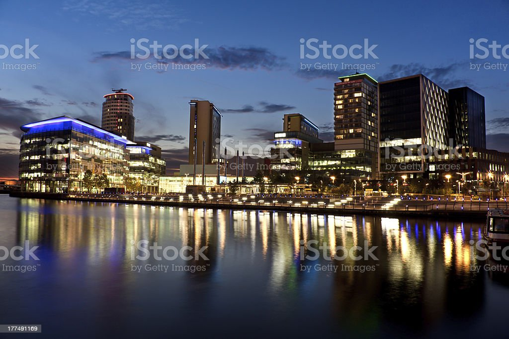 A beautiful media city lit up with lights next to the sea stock photo