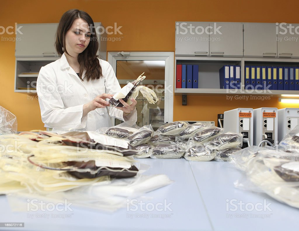 Beautiful medical worker in a blood bank...pile of bloodbags royalty-free stock photo