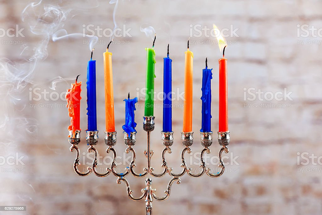 Beautiful menorah with burning candles on ligh stock photo