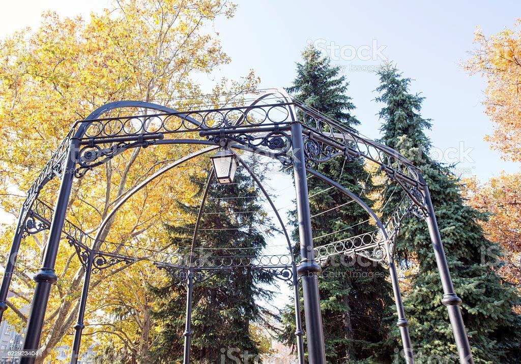 Beautiful metal gazebo under big old tree in park stock photo