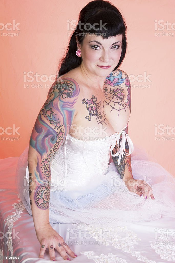 Beautiful mid adult pinup model in white on pink. stock photo