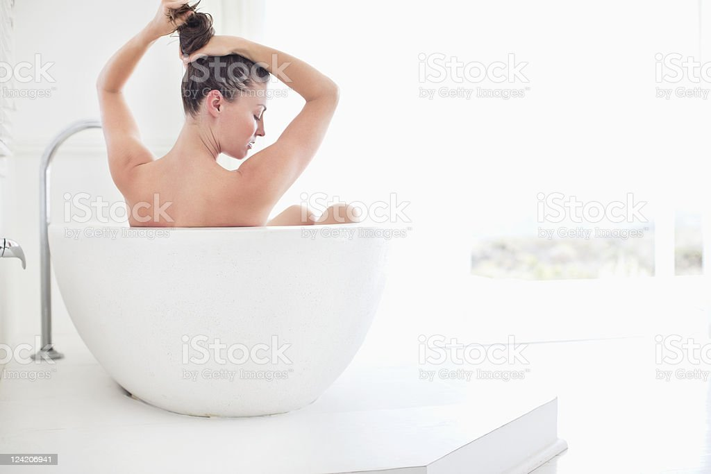 Beautiful mid adult woman in bathtub royalty-free stock photo