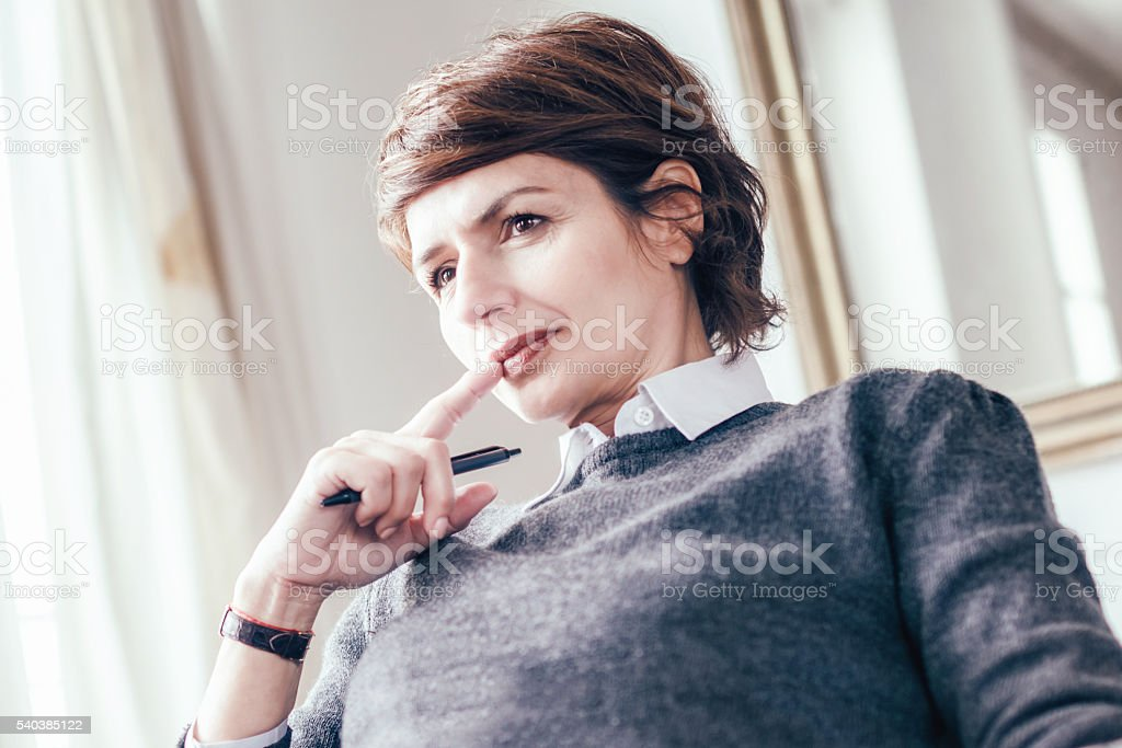 beautiful mid aged french business woman looking pensive stock photo