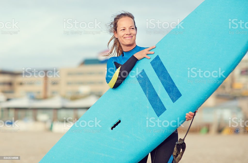 Beautiful middle aged female surfer on dutch beach stock photo