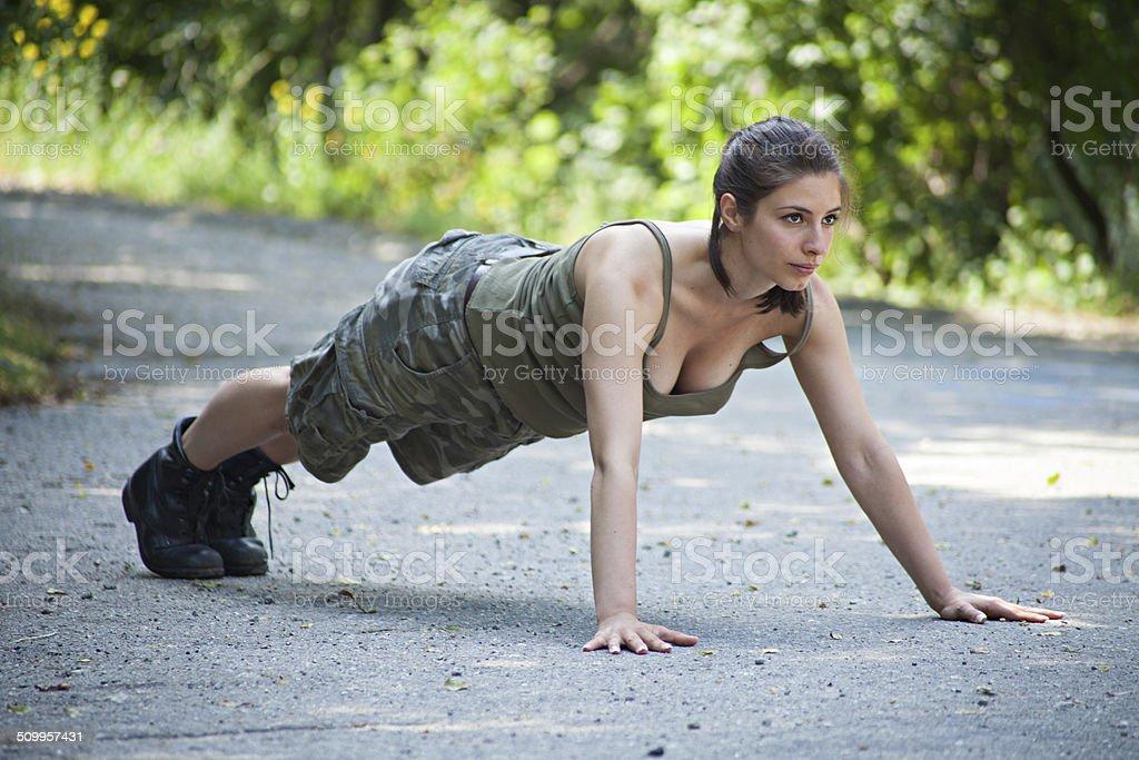 Beautiful military woman training in park - pushups stock photo