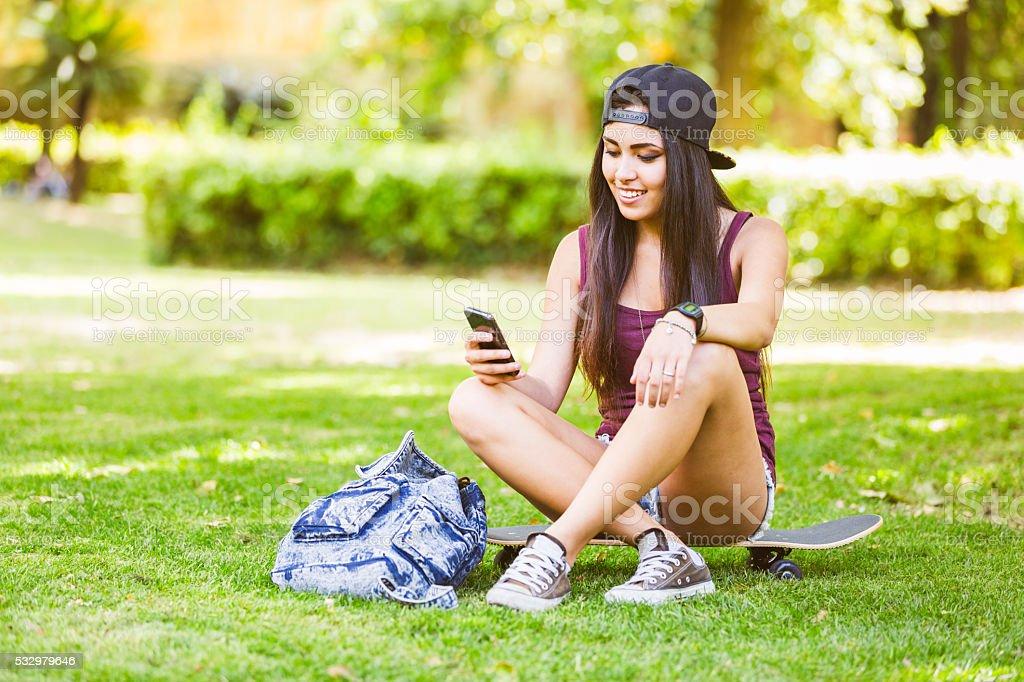 Beautiful mixed race girl looking at smart phone stock photo